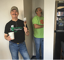 COO Rick Johnson and Director of IT Darren Scheller painting a house for Rebuilding Together
